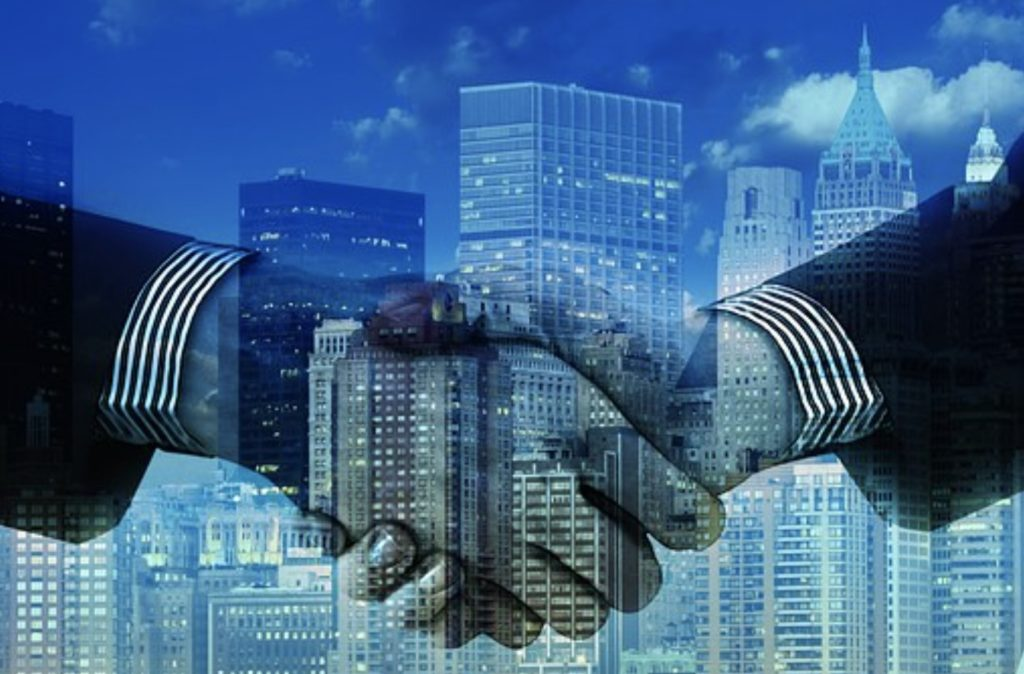 Crexendo merges with NetSapiens Podcast - Two male hands reach across a cityscape to shake hands, symbolic of the merger between two UCaaS companies that sell unified communications.